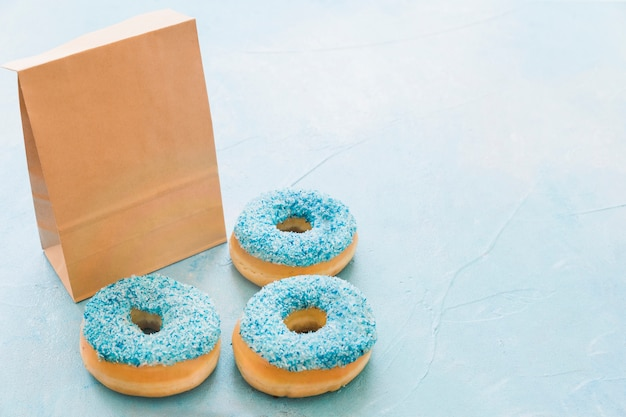 Fresh donuts with package on blue background