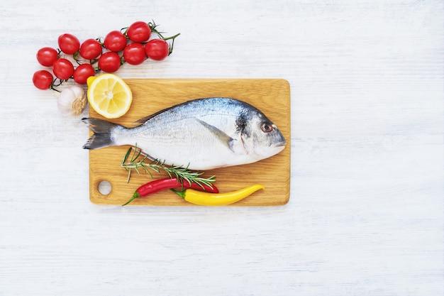 Свежая рыба дорада со специями на деревянной разделочной доске. концепция здорового питания. вид сверху, копировать пространство