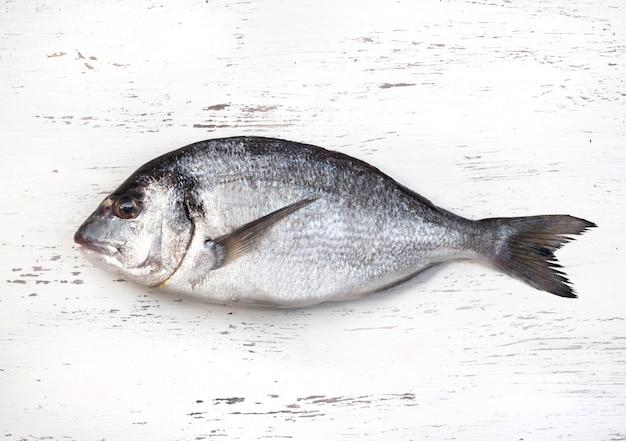 Свежая рыба дорадо на белом деревянном столе