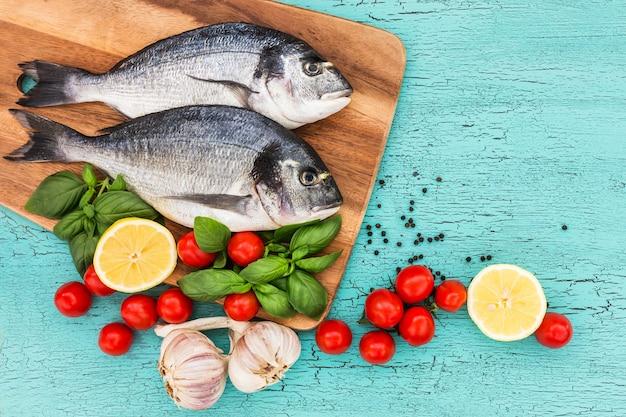 Свежая рыба дорадо на деревянной разделочной доске, помидоры, базилик, чеснок и лимон на синем столе. вид сверху