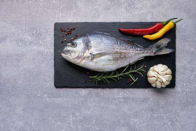 Fresh dorado fish on slate cutting board with garlic, rosemary, pepper, chilli pepper. copy space