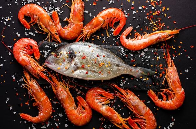 Fresh dorado fish and tiger prawns on black background