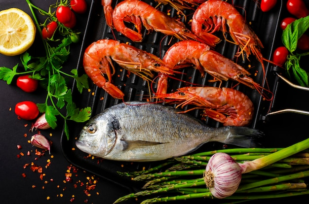Fresh dorado fish and tiger prawns on iron grill pan and vegetables for cooking