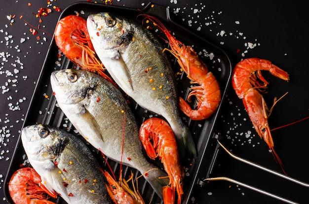 Fresh dorado fish and tiger prawns on iron grill pan