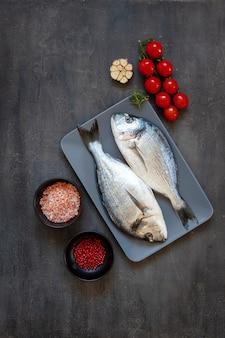 テーブルの上の黒いまな板にニンニクと調味料のスパイスと新鮮なドラド魚