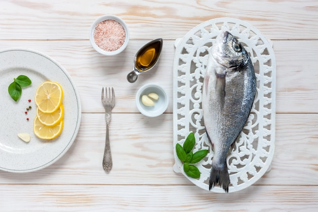 Fresh dorado fish with spices, olive oil, garlic and  seasoning on white dish on white table.