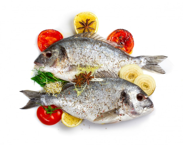 Fresh dorado fish with vegetables and spices isolated on white
