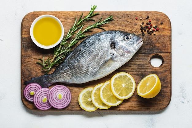 Свежая дорадо на разделочной доске с лимоном и специями, подготовленная для приготовления. вид сверху.
