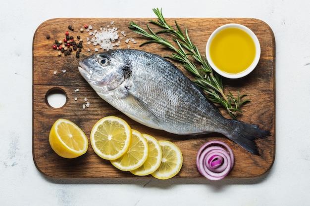 レモンとスパイスを調理用に準備したまな板の上の新鮮なドラド。上面図。