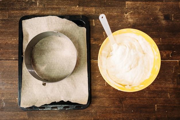 Свежее тесто в миске и сковороде с пергаментной бумагой на дереве