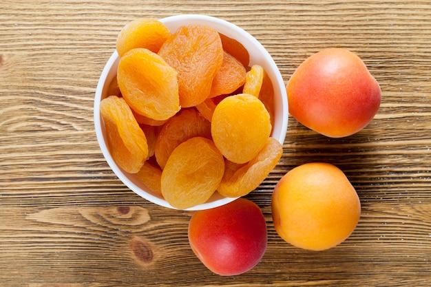 白いボウルに新鮮なドライアプリコットと木製のテーブルの上に一緒に横たわっている新鮮な果物、クローズアップ