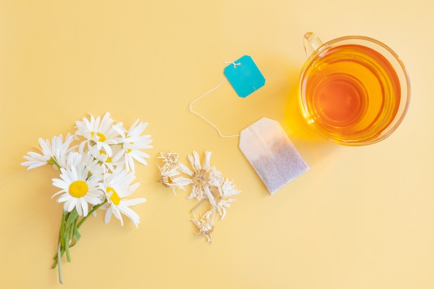 Fresh and dried chamomile flowers, a tea bag and a translucent cup of tea.