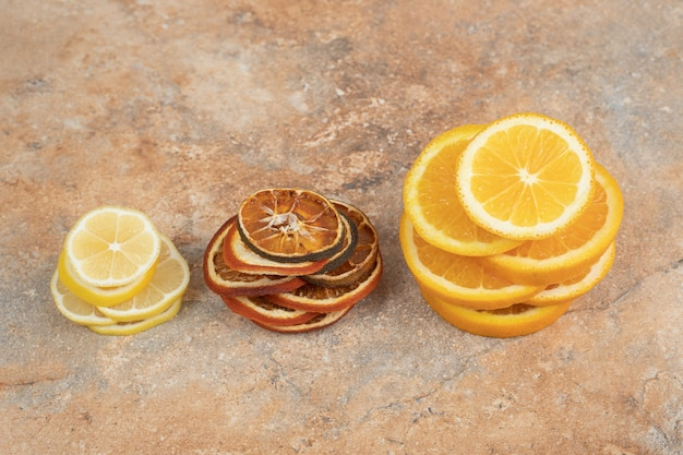 Fresh and dried lemon slices on marble surface.
