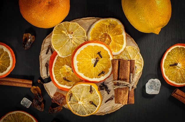 Fresh and dried oranges and lemons on black surface