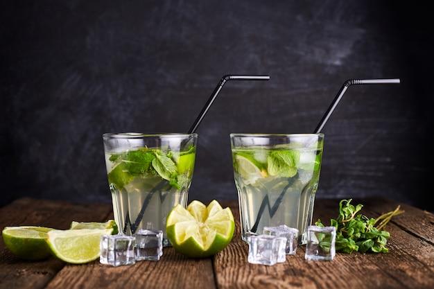 Свежий напиток с лаймом, мятой и льдом на деревянный стол на темном