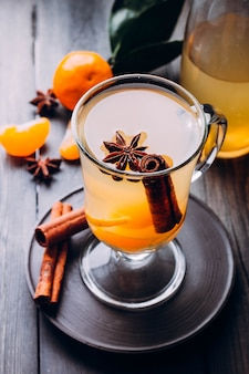 Fresh drinks with spicy,citrus fruits and cinnamon in glass on wood
