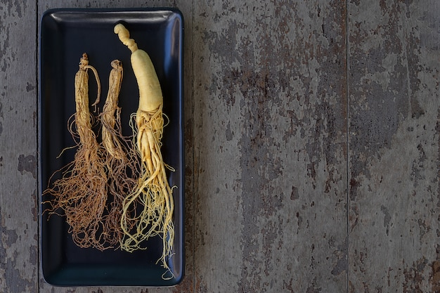 Fresh and dry ginseng on black plate with copy space on the wood background.