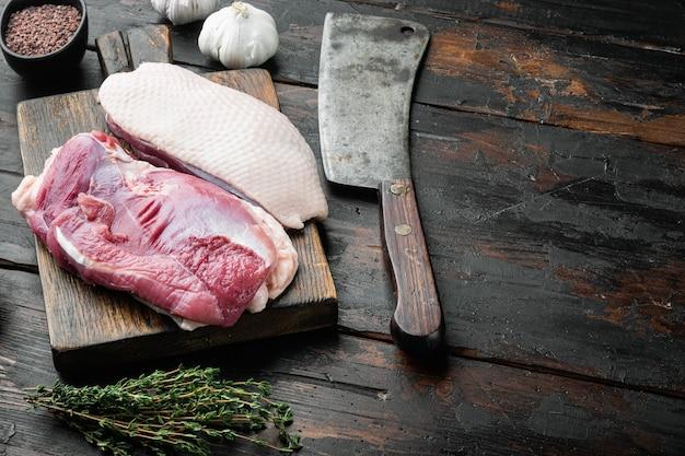 Свежее утиное мясо для еды, набор сырых утиных грудок, на деревянной разделочной доске со старым мясным ножом, на старом темном деревянном столе
