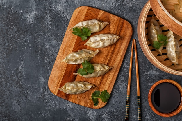 Fresh dumplings on a dark stone surface asian cuisine, top view, copy space.