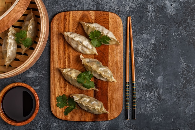 Fresh dumplings on a dark stone table.