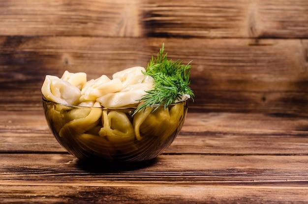 木製のテーブルの上のガラスのボウルに新鮮な餃子