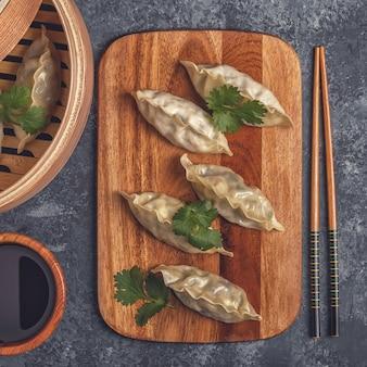 Свежие пельмени на разделочной доске с палочками для еды