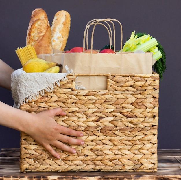 Свежие экологически чистые овощи, зелень и фрукты, крупы и макаронные изделия в плетеной корзине в руках ребенка. доставка или пожертвование концепции питания экологической фермы