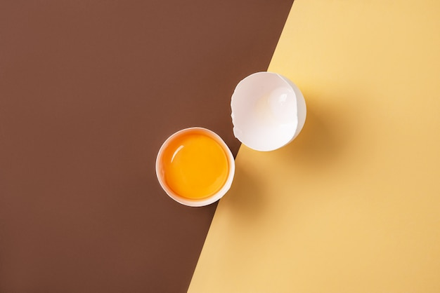 黄色と茶色の背景に壊れた新鮮な卵