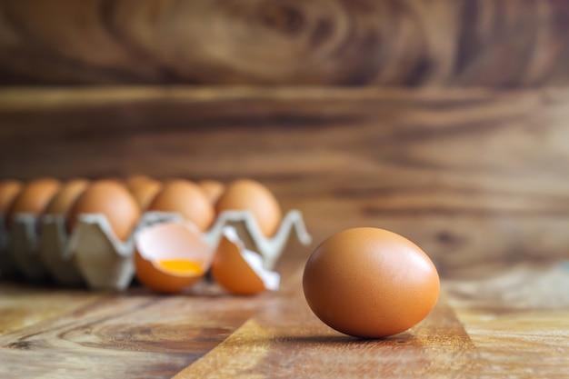 紙箱に新鮮な卵と卵殻の背景に卵黄と木製のテーブルに新鮮な卵。高タンパク質の食品成分。