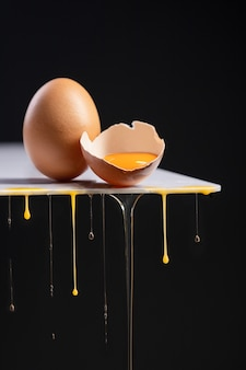 Свежее яйцо разливается на черном фоне.