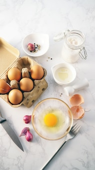 Fresh egg yoke in glass bowl surrounded with cooking ingredients