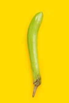 Fresh eggplant on yellow background.