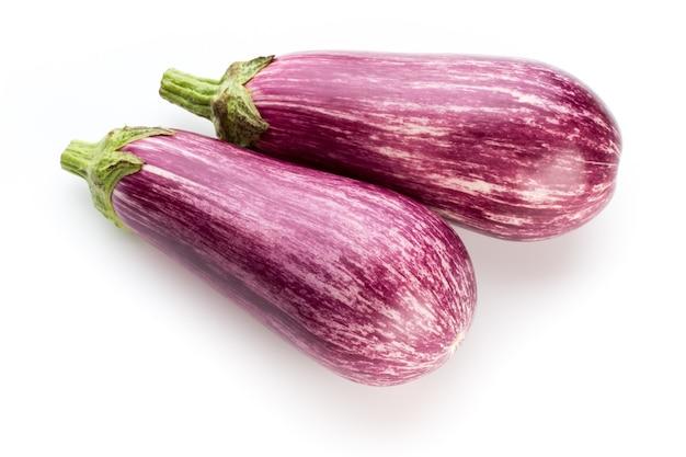 Fresh eggplants, aubergine on a white surface.