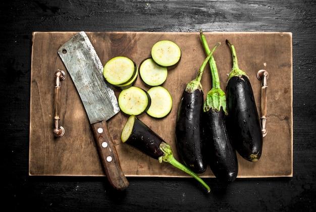 Свежие баклажаны со старым ножом и дольками на черной доске