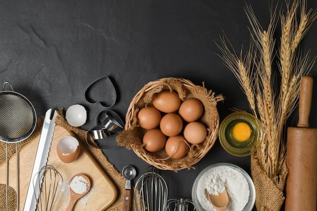 Свежие яйца и мука для торта с кухонной утварью для выпечки на черном столе