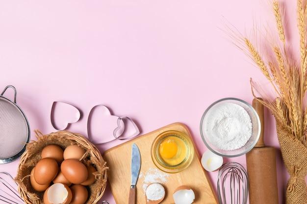 Свежие яйца и мука для торта с кухонной утварью для выпечки на розовом фоне, подготовка к приготовлению торта и концепции пекарни