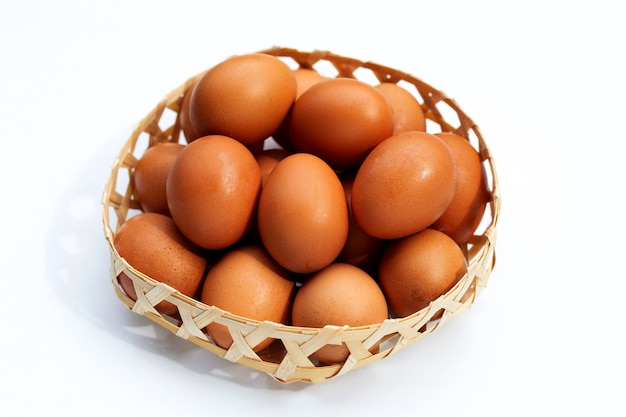 Fresh eggs in bamboo basket on white background.