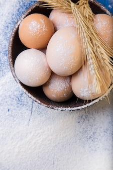 Fresh eggs in a brown bowl on flour . top view