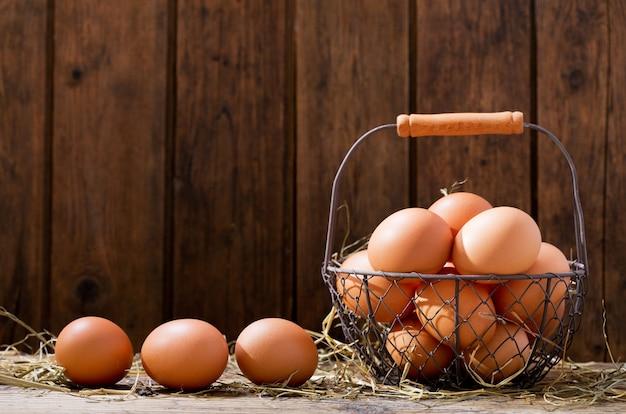 Свежие яйца в корзине на деревянном столе