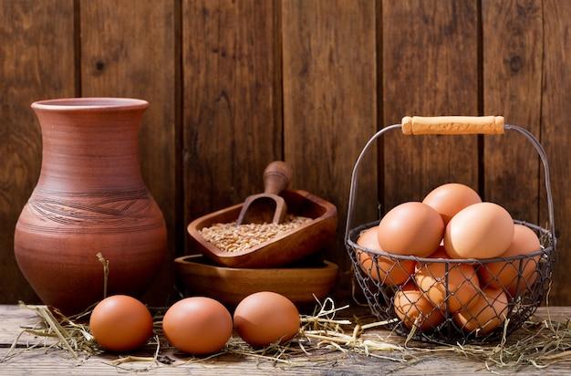 木製のテーブルの上のバスケットに新鮮な卵