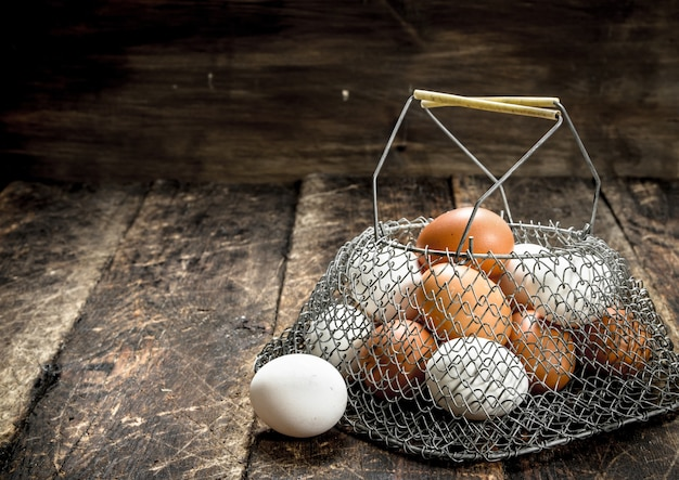 メッシュバッグに入った新鮮な卵。木製の背景に。
