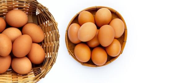 白い背景の上の竹かごの新鮮な卵。コピースペース