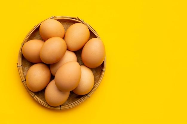黄色の背景に竹かごの中の新鮮な卵。コピースペース