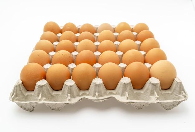 Свежие яйца в упаковке на белом фоне.
