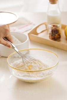 Свежее яйцо, молоко и мука на белом столе