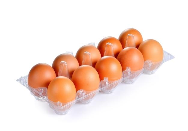 Свежие яйца на пластиковом подносе
