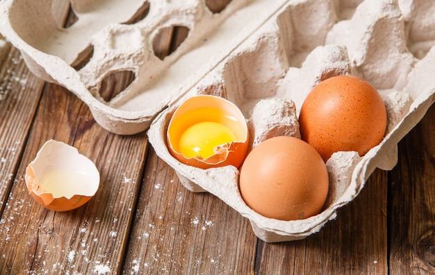 Fresh eggs, one of which was broken, on a wooden table.