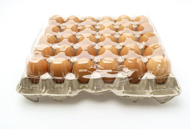 Fresh eggs in package on white background .