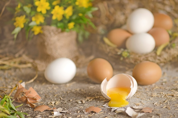 Fresh eggs in straw with rustic wooden background. raw chicken egg yolk broken