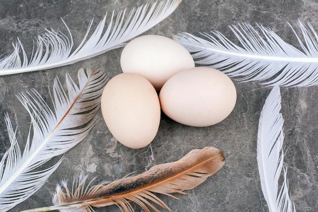Свежие яйца с перьями на мраморном фоне. фото высокого качества